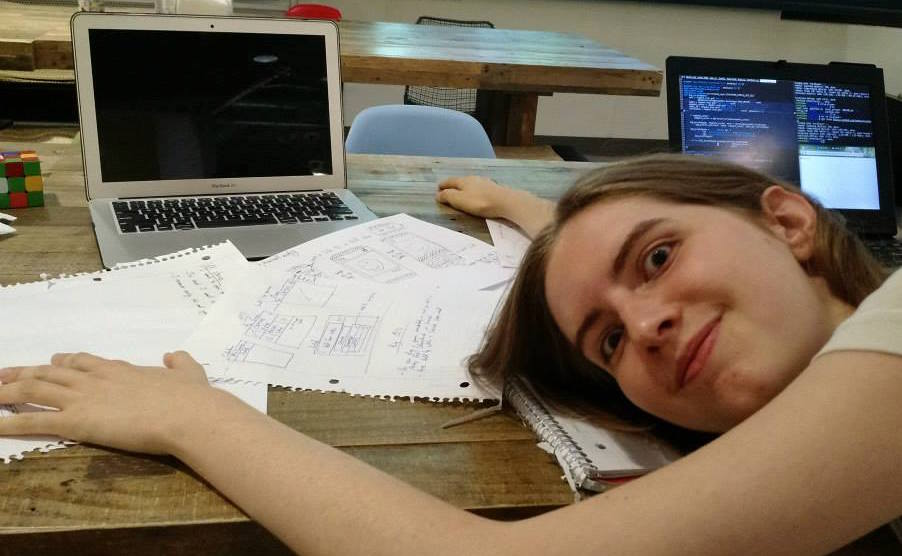 A picture of Chelsea laying her head down on a bunch of paper.